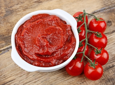 Tomato paste with ripe tomatoes on wooden tables