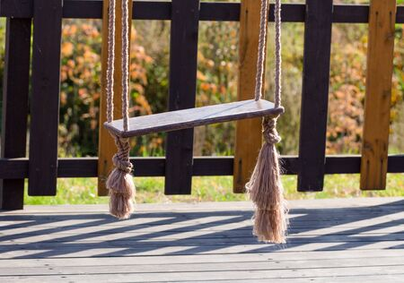 Photo pour Swing on the playground close-up on a background of a wooden fence. - image libre de droit