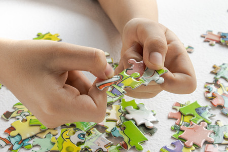 Foto de Puzzles with baby handles, Children's hand with colored toy puzzles. Early learning - Imagen libre de derechos