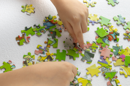 Photo pour Close up of child's hands playing with colorful puzzles on light table. Early learning. child plays puzzles - image libre de droit