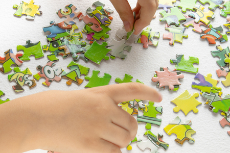 Photo pour child plays puzzles, hands of a child playing colorful puzzles - developing a child through playing toys - image libre de droit