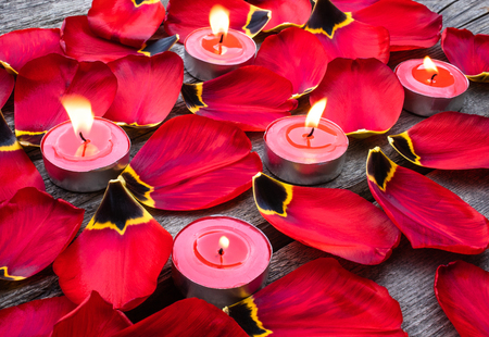Photo pour Fallen, red tulip petals near burning candles. A candle is burning near the tulip petals. - image libre de droit