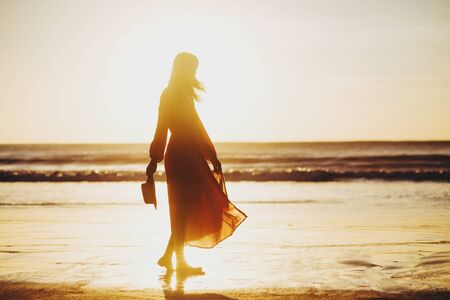Photo pour young slim beautiful woman on sunset beach, playful, dancing, running, bohemian outfit, indie style, summer vacation, sunny, having fun, positive mood, romantic, splashing water, silhouette, happy - image libre de droit
