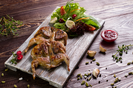 Roasted quails with  salad and  spices on a wooden board.
