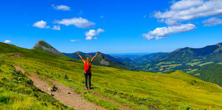 Photo for back view of backpacker tourist girl on the mountain in France, Cantal - Royalty Free Image