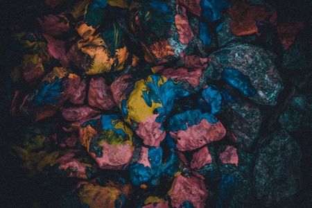 dark abstract background of stones covered with multi-colored paint