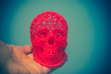 Skull printed with plastic of red color on a 3d printer. Skull printed on 3d printer in mans hand. Progressive modern additive technology