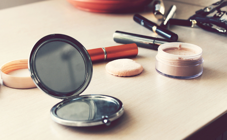 Mirror, powder, puff, mascara, eyeliner and other cosmetics on the table