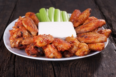 Buffalo chicken wings on plate with blue cheese sauce and celery.