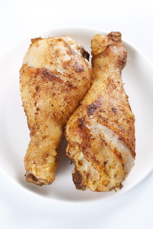 Two roasted chicken legs on plate on white background