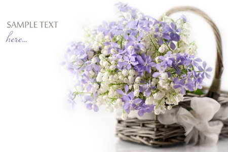 Bouquet of spring flowers in basket on white background