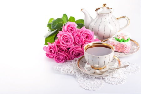 Closeup of cup of tea with cake and roses