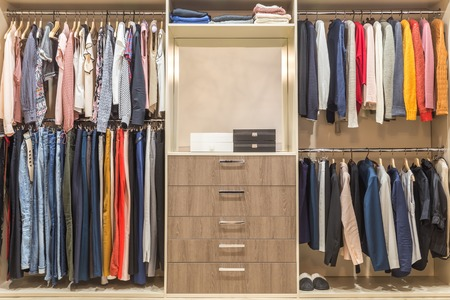 Photo pour Modern wooden wardrobe with clothes hanging on rail in walk in closet - image libre de droit
