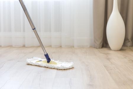 Photo pour Cleaning floor with white mop near sofa - image libre de droit
