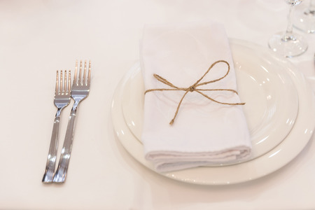 Photo pour Plate, forks, napkin and knife in restaurant - image libre de droit