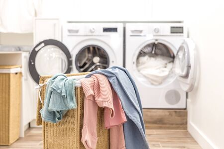 Photo pour Laundry basket with dirty clothes with washing and drying machines on the background - image libre de droit