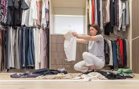 Photo pour Young woman throwing clothes in walk in closet. Mess in wardrobe and dressing room - image libre de droit