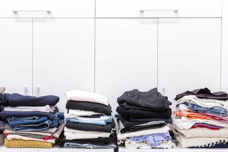 Photo pour Stacks of clean clothes in utility room - image libre de droit