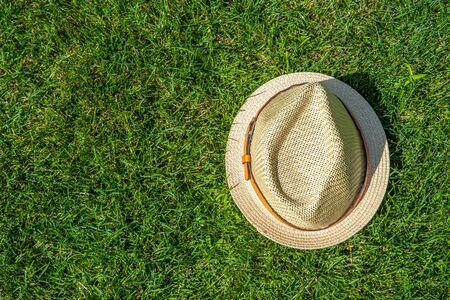 Foto de Straw hat on the green grass background - Imagen libre de derechos