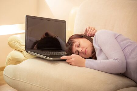 Photo pour Tired freelance worker woman sleeping right on her laptops keyboard on a couch - image libre de droit