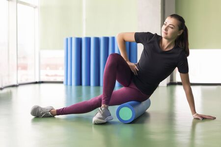 Photo for Attractive female doing foam roller exercise and posing in modern bright fitness center - Royalty Free Image