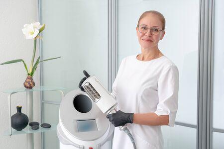 Foto de cosmetologist standing in rubber gloves doing endospheres therapy - Imagen libre de derechos