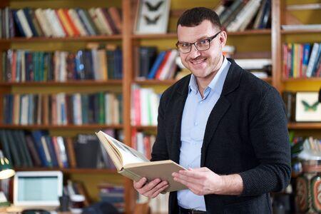 Foto de Man reading book in college library many books on a background - Imagen libre de derechos
