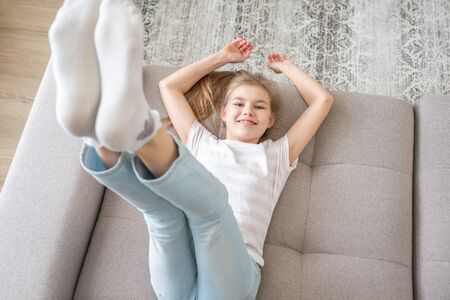 Foto de Preteen girl lying on couch with her feet raising up high - Imagen libre de derechos