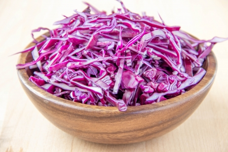 Shredded red cabbage in wooden bowl