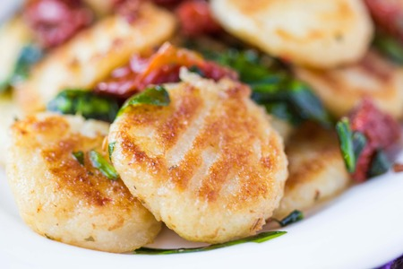 Fried potato gnocchi with sauce of dried tomatoes, spinach, Italian delicious homemade dish