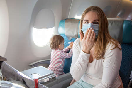 Photo pour a young mother is sitting in an airplane chair in a medical respiratory mask with a scared face loking in camera. concept emotion fear coronavirus covid-19 - image libre de droit