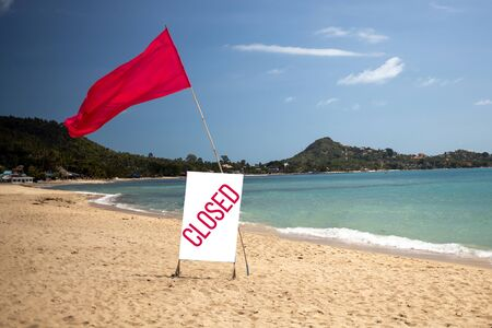 concept quarantine, pandemic, coronavirus, stay home. tropical beach on a sunny day without people. there is a red flag and a sign saying closed.