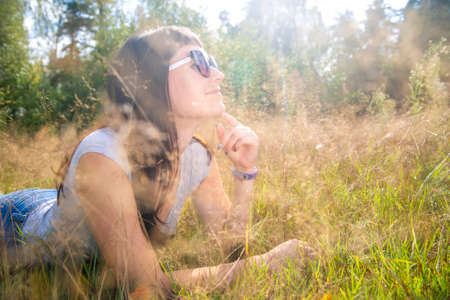 Foto per beautiful young woman in sunglasses enjoys the sun on the grass in warm sunshine - Immagine Royalty Free
