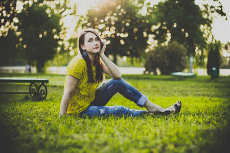 Photo pour Young beautiful woman in yellow blouse and blue jeans sitting in a park on the grass holding head on hand and smiles in the warm summer evening. Photo of a girl with back sunlight on the nature. - image libre de droit