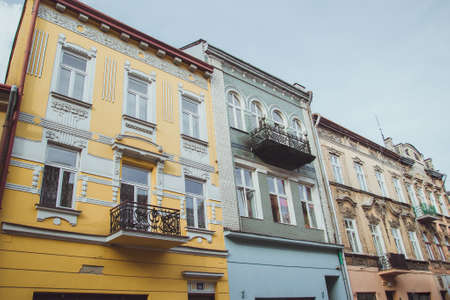 Photo pour A low angle shot of colorful tenament houses facades in old town of Przemysl, Poland. Colorful old buildings in city center, houses with ornate yellow, blue and beige walls. - image libre de droit