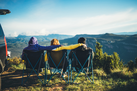 Photo pour three friends sit in camping chairs on top of a mountain, travelers enjoy nature and cuddle, tourists look into distance on background of panoramic landscape, weekend concept - image libre de droit