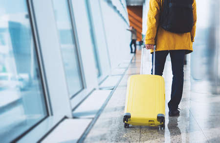 Photo pour traveler tourist in bright jacket with yellow suitcase backpack at airport on background large window blue sky, man waiting in departure lounge area, hall of ​airport lobby terminal, vacation trip concept, empty space mockup - image libre de droit