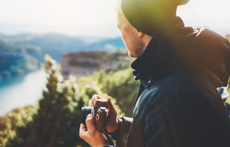 hipster tourist hold in hands taking photography click on retro vintage photo camera in auto, photographer looking on camera technology, hobby content, sun flare mountain, panoramic landscape vacation concept