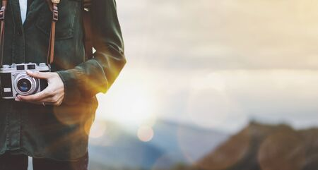 Photo pour Hipster young girl with bright backpack taking photo of amazing landscape sunset on vintage camera close on peak of foggy mountain mockup. Tourist traveler on background sunlight in trip in northern spain basque country, mock up for text. - image libre de droit