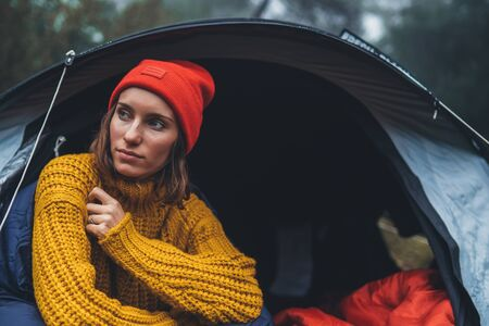 tourist traveler ralaxing in camp tent in froggy rain forest, closeup lonely hiker woman enjoy mist nature trip, green trekking tourism, rest vacation concept camping holiday