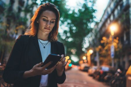 Photo pour Young stylish business woman writes message on smartphone walking evening city street, hipster tourist traveling in european town and planning trip using mobile phone - image libre de droit