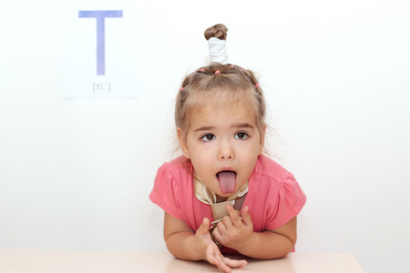 Photo for Pretty small girl wearied a tie sticking her tongue out over white background with T letter on it, indoor portrait - Royalty Free Image