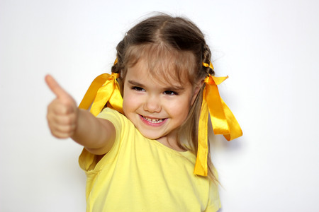 Cute little girl with yellow bows and yellow T-shirt showing thumb up gesture over white background, sign and gesture concept