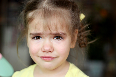 Cute preschooler blond girl crying and looking at camera over dark background, emotional closeup portrait, upbringing and family concept