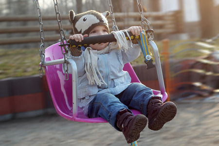 Brave cute toddler boy having fun and flying on a chain swing carousel in the park, first sunny day in spring, happy family and childhood concept, outdoor closeup portrait