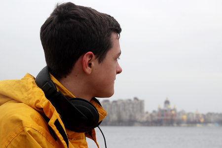 Handsome teenage boy in yellow coat with ear-phones and a bunch of yellow tulips waiting for a date on the bank of the river in a big city, outdoor portrait