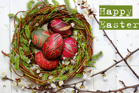 Decorated willow nest with colored Easter eggs, pysanky, blossoming flower, Ukrainian history and culture, family holiday, focus on eggs in nest