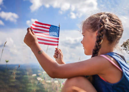 Photo pour Patriot and National Flag day celebration. Cute little patriot sitting on the meadow and holding the national flag of United States over blue sky background, summer outdoor, soft focus on flag - image libre de droit