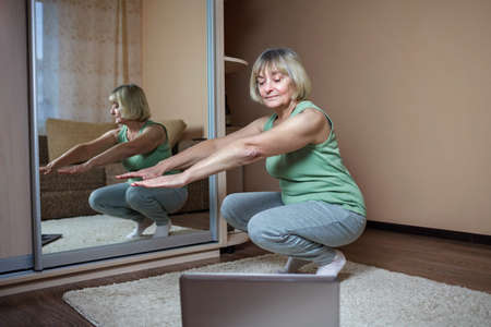 Senior woman in sportswear watching online video on laptop and doing fitness exercises at home. Distant training, social distance, self-isolation, hobby, wellness and online education concept