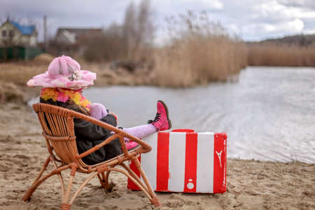 Foto de Cute girl in a coat and flowers garland sitting on beach in cold early spring day and enjoying beautiful view, outdoor, ready for summer, holiday and travel concept, adaptation and lockdown reality - Imagen libre de derechos